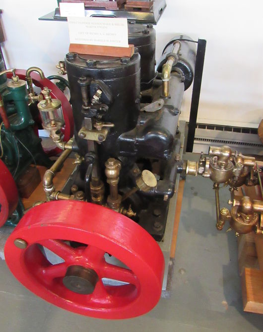 Mianus 2 Cylinder Marine Engine MA084 end view. Black cylinders and red flywheel.